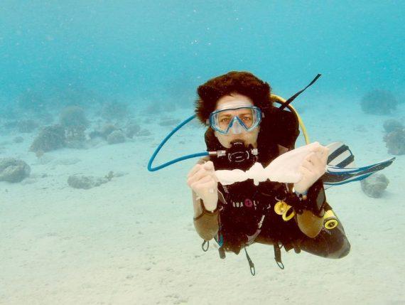 Une plongeuse avec un sac plastique sous l'eau