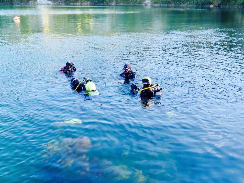 Des plongeurs s'apprêtent à s'immerger dans un plan d'eau
