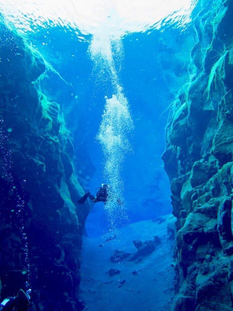 Un voyage plongée en Islande ne peut s'envisager sans une plongée dans la faille comme pour ce plongeur dans la grande crevasse de la faille de Silfra