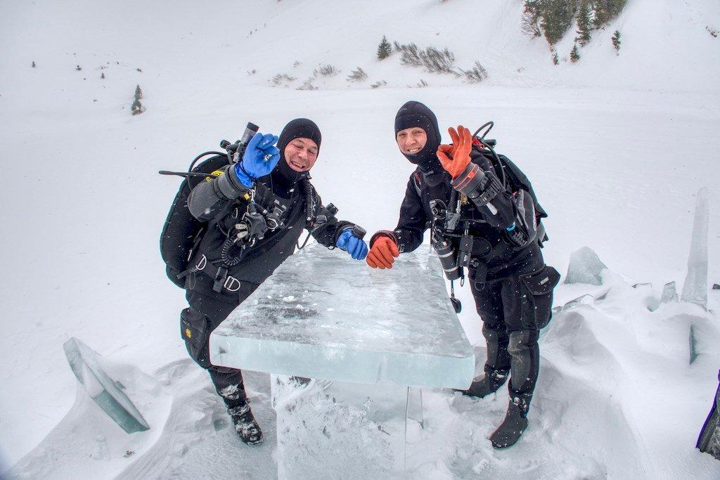 Deux plongeurs font le signe OK autour d'une table sculptée dans la glace.