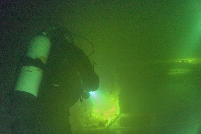 Un plongeur dans l'eau sombre de la carrière