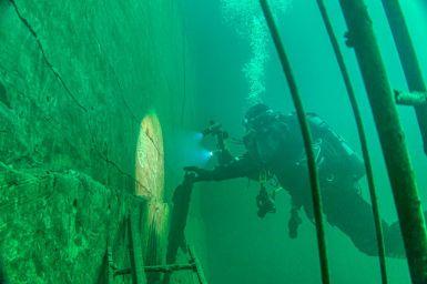 Mon binôme me montre des gravures anciennes sous l'eau à la carrière de Vodecée.
