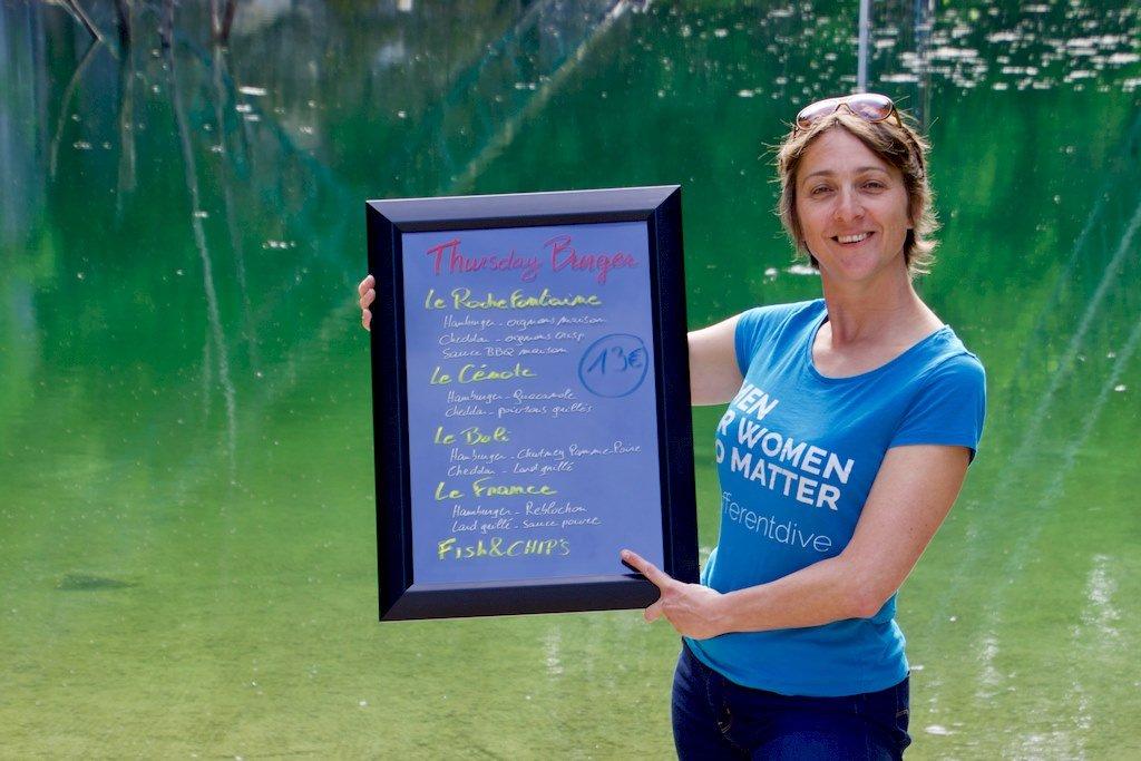 Hélène tien le panneau où les noms des hamburgers de Rochefontaine sont indiqués