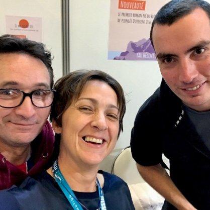 Deux internautes souriants entourent H2lène Adam au salon de la Plongée de Paris.