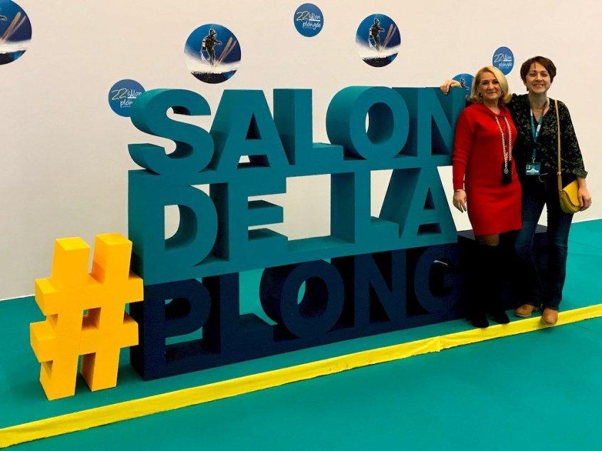 Hélène Adam et Hélène de Tayrac pose devant l'insigne du Salon de la Plongée 2020