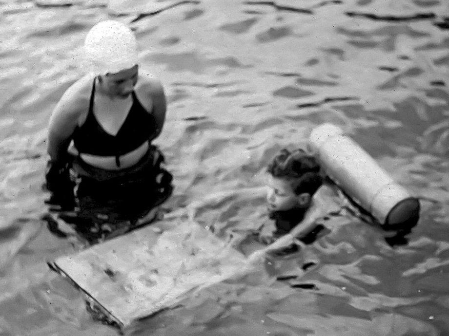 Une dame apprend à un garçonnet à nager.