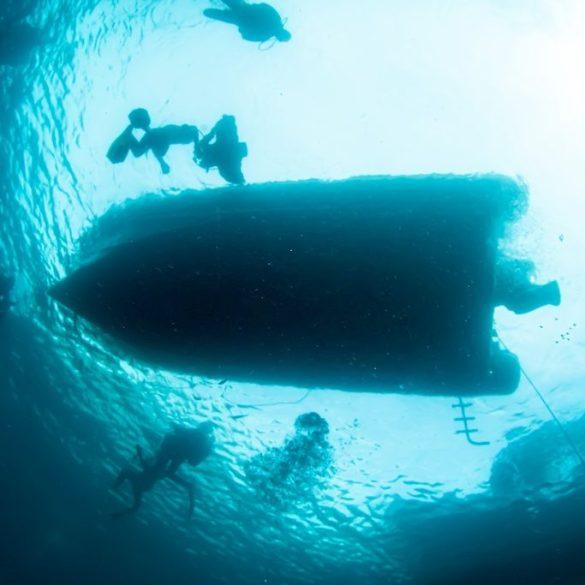 Un bateau de plongée vu du dessous emmène des plongeurs pour une expéditions dans le climat de plongée et coronavirus.