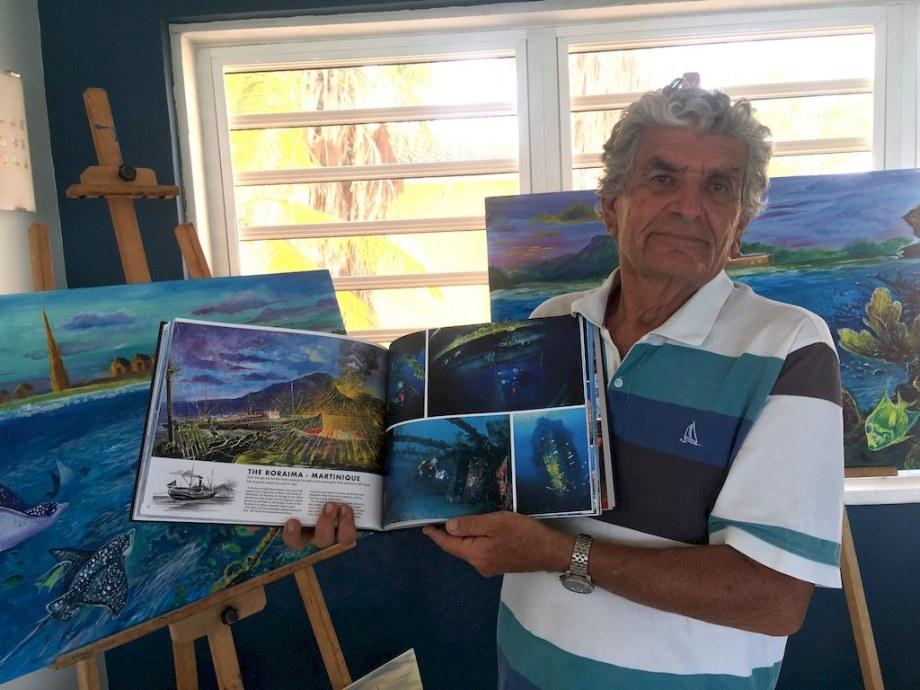 """Dominique tient son livres """"les bulles de la Calypso"""" devant ses peintures."""
