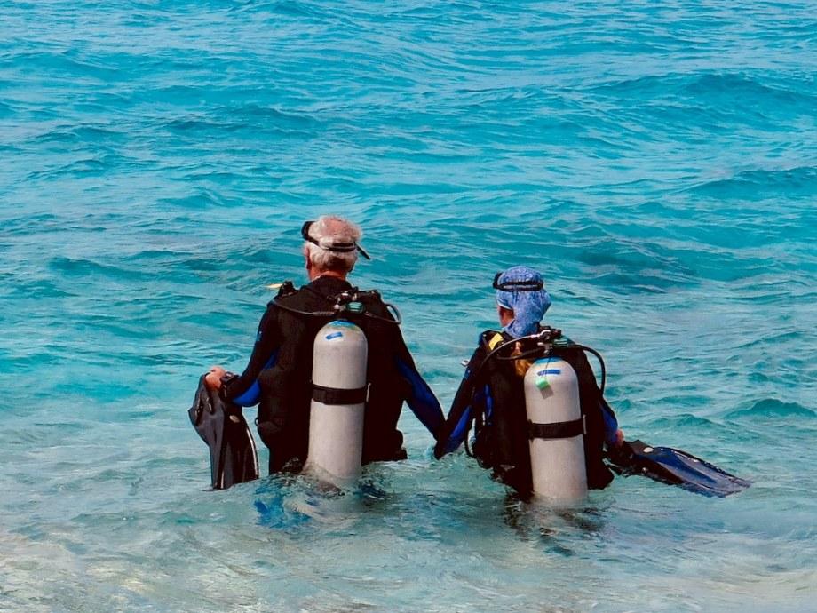 Plongée et ménopause demande parfois du soutien comme pour cette dame aidée par son mari à entrer dans l'eau à Bonaire.