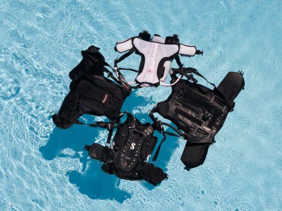 Choisir un gilet ou stab de plongée n'est pas toujours simple face au choix comme pour ces 4 gilets qui flottent dans une piscine.