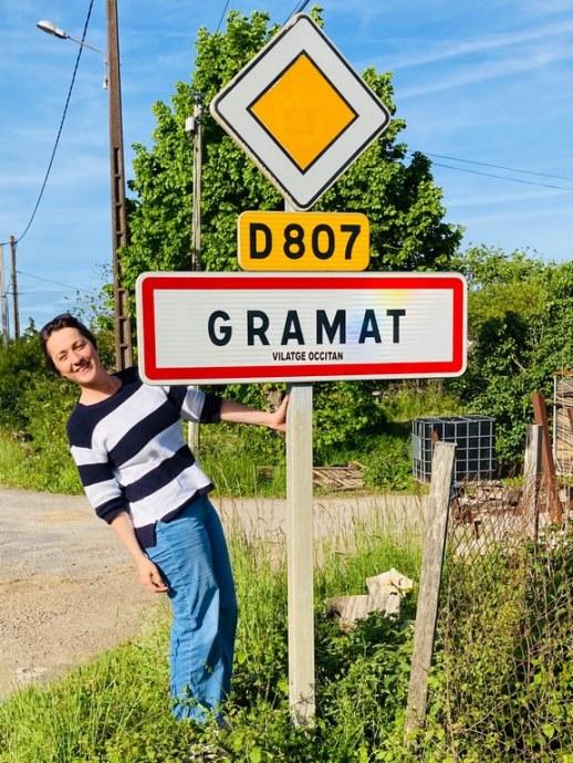Hélène Adam devant le panneau d'entrée de la commune de Gramat.