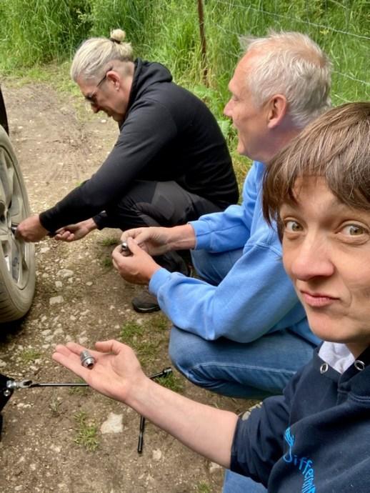Hélène Adam, Mike Doumont et Didier réparent un pneu crevé.