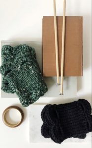 Two Marilue cowls are artfully places on top of some books. The colors shown are green tweed and black.