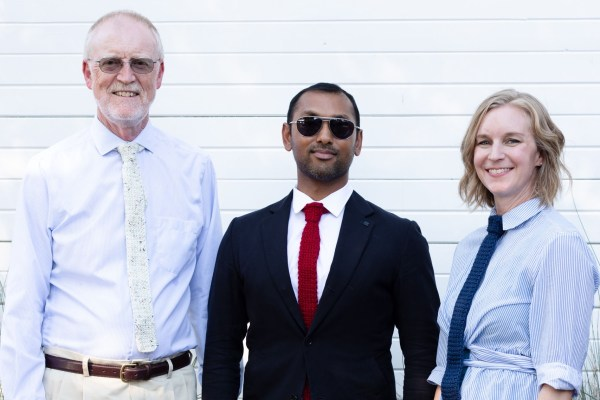 3 people stand together. One man wears a white shirt and an ivory tweed knitted necktie. The other man wears a black blazer, white shirt and red knitted necktie. The woman wears a blue and white shirt and a blue knitted necktie.
