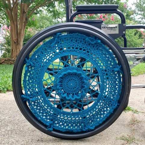 A wheelchair is shown with a dark teal wheel cover. The wheel cover is crocheted by hand with open work and 3D texture