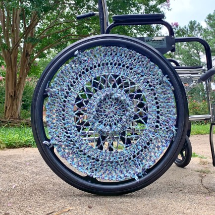 A wheelchair is shown with a variegated blue wheel cover. The wheel cover is crocheted by hand with open work and 3D texture.