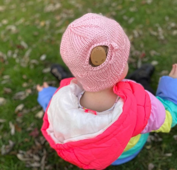 A toddler looks away from the camera. She is wearing a pink hat with an opening for her cochlear implant sound processor.