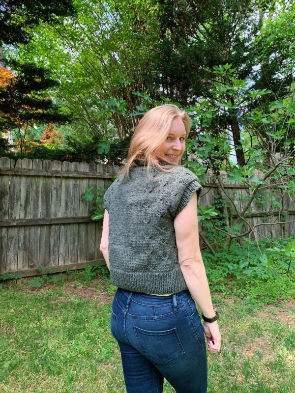A blond woman is wearing a green knitted cardigan and jean. She is facing away from the camera and looking over her shoulder.