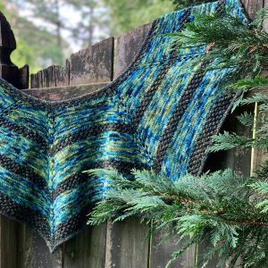 A blue and green shawl is draped over a wooden fence. Some evergreen branches are in front of the shawl on the right side.