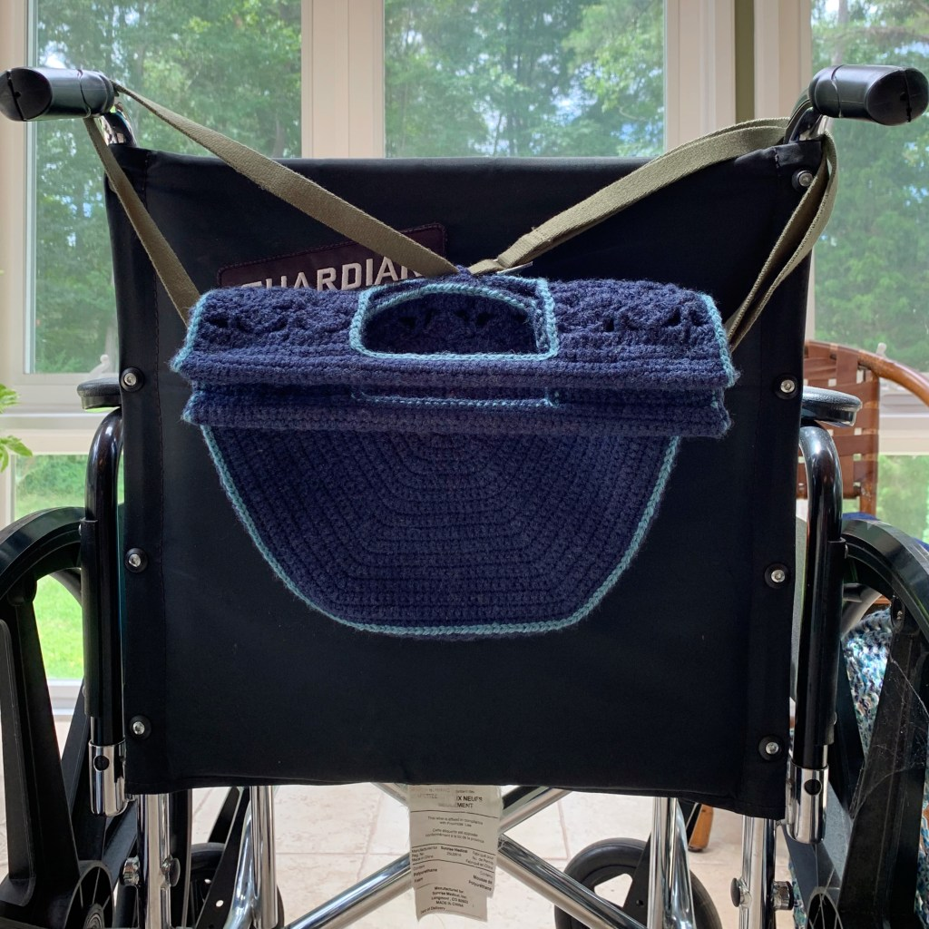 A manual wheelchair is shown from the back.  A blue crocheted purse is hanging from the back by an olive bag strap