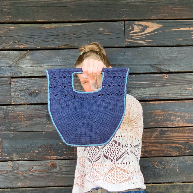 A blond woman in a white sweater is holding p a blue crochet purse and is looking through the hole made by the handle