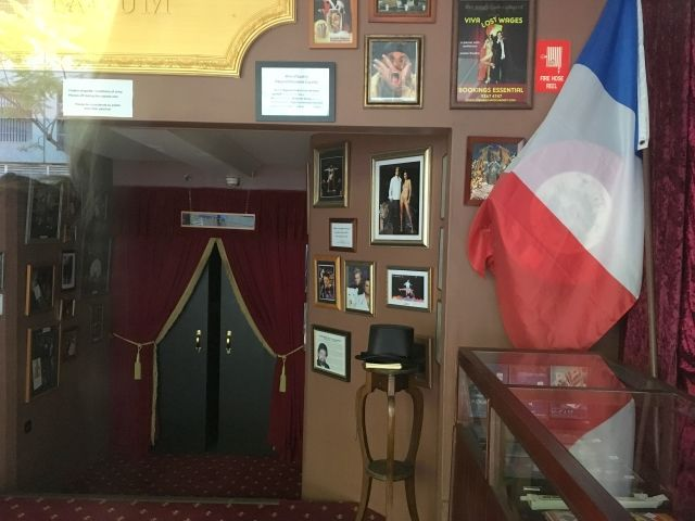Foyer of the Australian Museum of Magical Arts. It has a french flag and pictures of famous magicians like Seigfried and Roy. There's a top hat on a chair.
