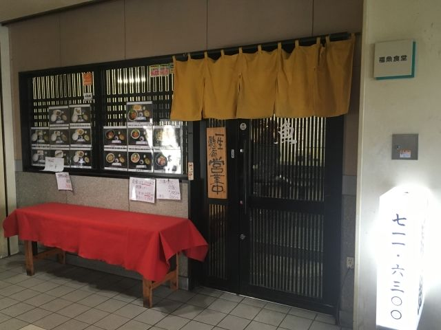 Outside of a simple restaurant in Fukuoka Fish market. It has a brown screen wood door with a beige curtain across it and pictures of dishes in the window