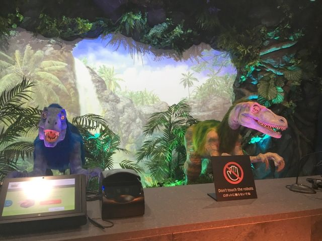 Reception of the Robot Hotel in  Fukuoka is manned by two dinosaurs one green and one blue surrounded by rocks and leaves.