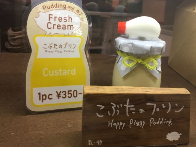 Small pot full of custard dessert. On top is a little paper cap and a small plastic pig.