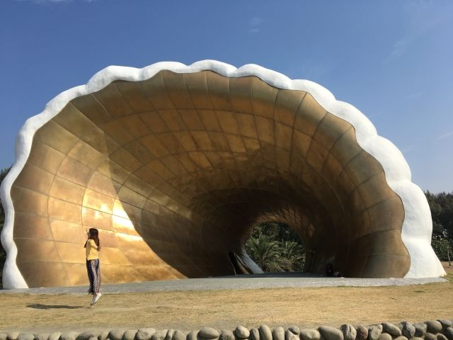Giant seashell sculpture with a girl jumping in front of it