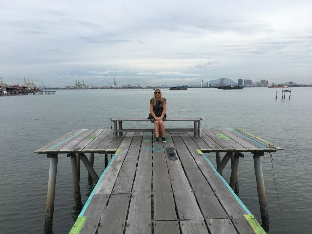 Girl sitting on a bench on the end of a wooden jetty
