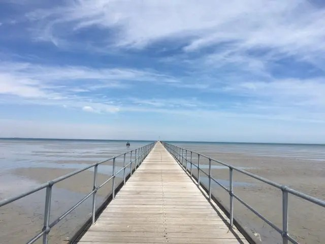 Long pier stretching into the distance with sea and blue sky behind