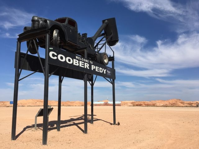 Black sign with a craon top saying Welcome to Coober Pedy