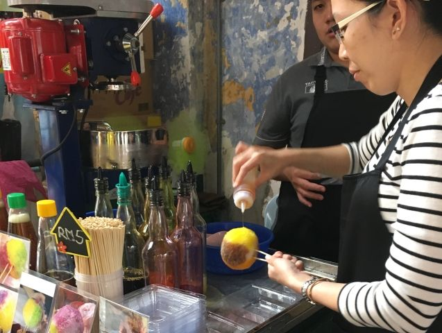 woman pouring honey on a ball of ice