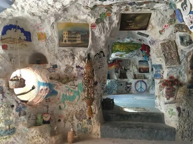 dug out cave home covered with graffiti and paintings