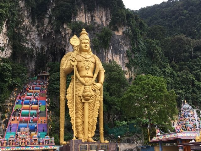 image of gold statue and a set of rainbow coloured steps at Batu Caves