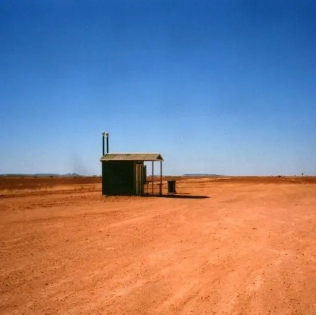 Toilet in the Australian outback with nothing around it but red earth.