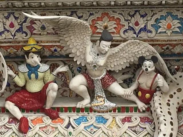 Carvings including Pinocchio and Mickey Mouse at Wat Pariwat, Bangkok