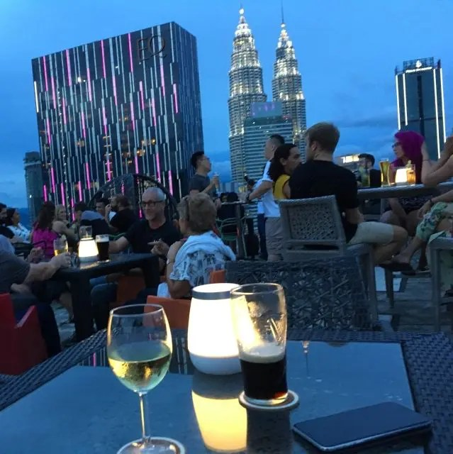 Drinks on a table with a view of the Petronas Towers in the background. At the HeliLounge bar, Kuala Lumpur
