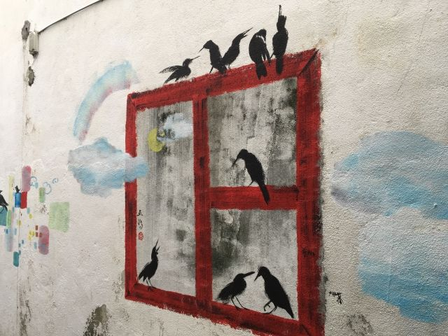 Mural of birds sitting on a window