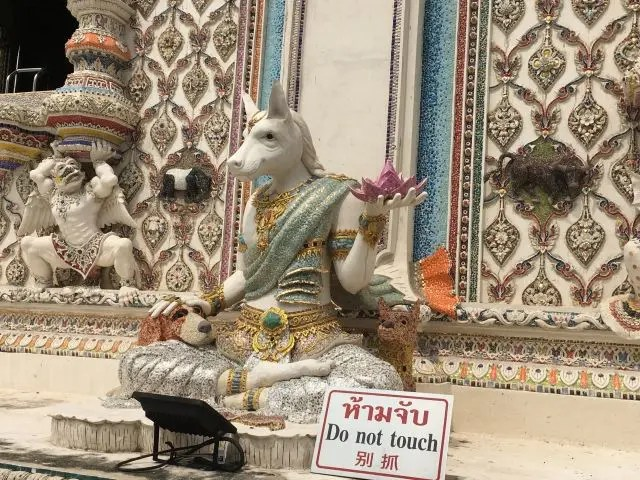 Cow statue with two dogs behind it at Wat Pariwas, Bangkok