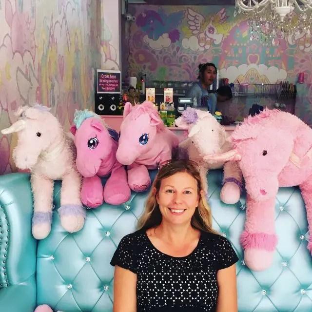 Woman sitting on sofa surrounded by cuddly unicorns at the Unicorn Cafe, Bangkok