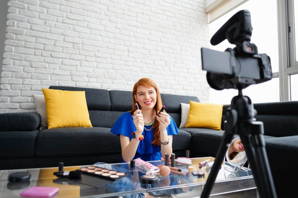 Happy girl at home talking about makeup in front of camera. People and technology, young woman at work as vlogger. Web influencer recording message for internet social networks
