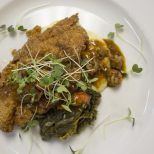 Guests at Jay Ducote's James Beard Preview Dinner enjoy crawfish etoufée-smothered fried catfish Friday, July 8, 2016 at the Louisiana Culinary Institute.