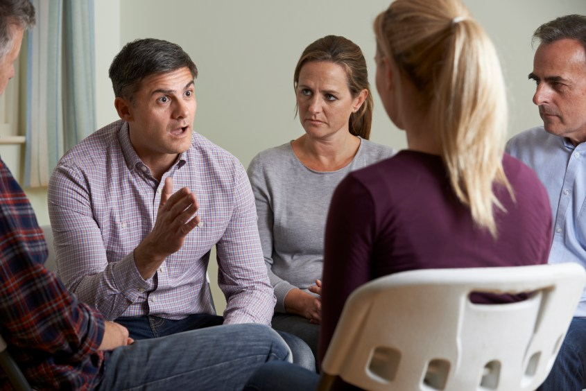 Members Of Support Group Sitting In Chairs Having Meeting