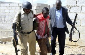 Police officers arrest a man found looting in Lusaka's Chaisa Township-picture by Tenson Mkhala