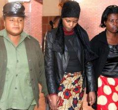 Precious Longwe ( c) being taken back to cells at Lusaka's Magistrates Court