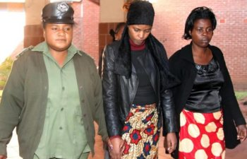 Precious Longwe ( c) being taken back to cells at Lusaka's Magistrates Court