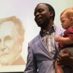 Dr Henry Musoma holds baby Emmett as he lectures