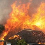 Generic image of grass thatched building on fire